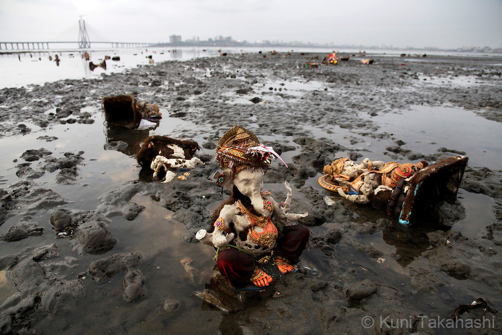 Half dissolved Ganesha idles are seen at low tide in Mumbai, India on Sep 19, 2010 during Ganpati festival. The immersion of the idols, which are made of plasters and other toxic materials, cases some environmental concern. The 10-day hindu festival, celebrating the birthday of Lord Ganesha who is widely worshiped as the god of wisdom, prosperity and good fortune, attracts tens of thousands people..Photo by Kuni Takahashi