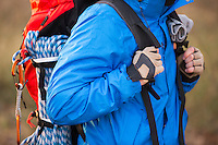 Midsection of male hiker carrying backpack outdoors