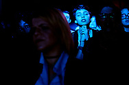 Bathed in blue light, a parishioner prays during the service at a rock n' roll church in Miami, FL.