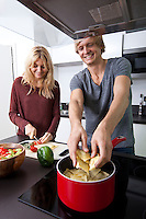 Happy man cooking pasta with woman in kitchen