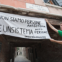 """VENICE, ITALY - MAY 27:  A protester from the group """"Democracia Real Ya"""" holds a signin support of popular democracy, on May 27, 2011 in Venice, Italy. The protest takes place on the day when Spanish police fired rubber bullets to disperse anti-crisis protesters in a Barcelona square as cleaning crews cleared their tent camp."""