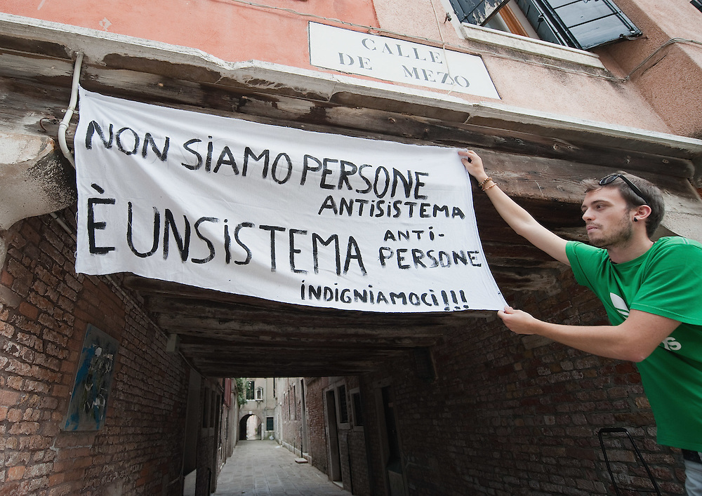 "VENICE, ITALY - MAY 27:   A protester from the group ""Democracia Real Ya"" holds a sign in support of popular democracy, on May 27, 2011 in Venice, Italy. The protest takes place on the day when Spanish police fired rubber bullets to disperse anti-crisis protesters in a Barcelona square as cleaning crews cleared their tent camp."