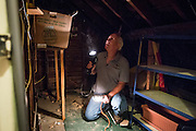 Mike Lehman from the Coporation for Appalachian Development (COAD) inspects the attic at 86 West State Street during an energy audit on Wednesday, June 24, 2015.  Photo by Ohio University  /  Rob Hardin