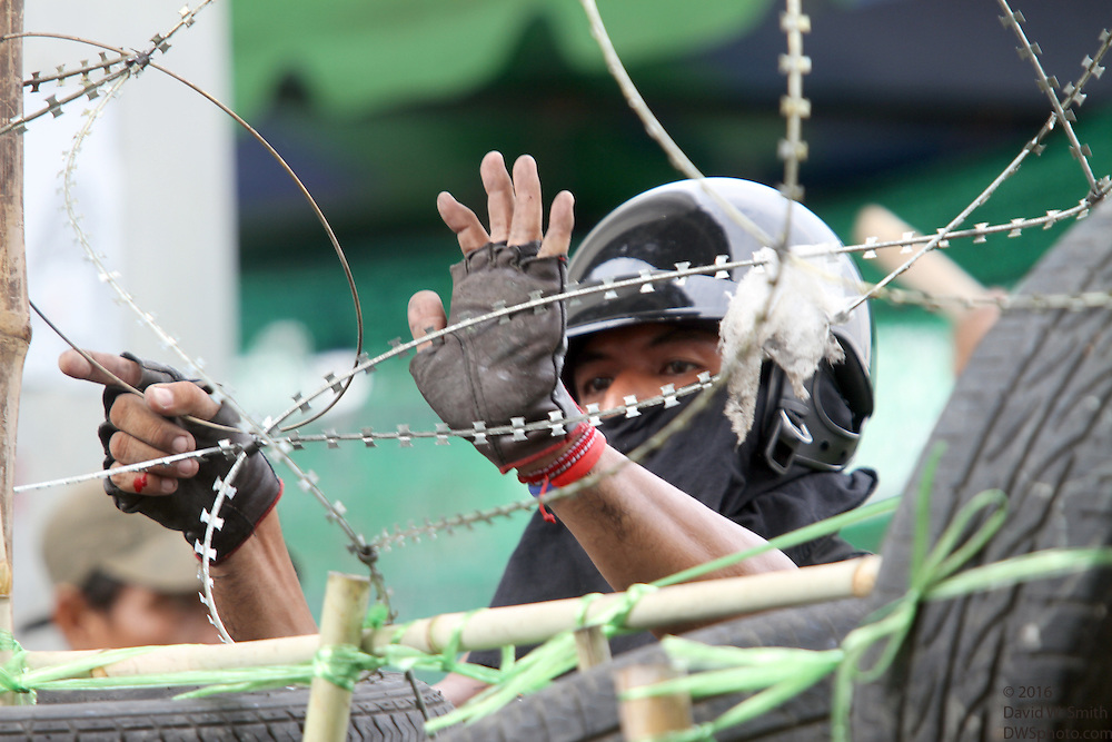 A helmeted protestor fastens barbed wire to a barricade during the Red Shirts anti-government protest in the Silom area of Bangkok.