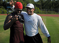 18 JULY 2011 -- ST. CHARLES, Mo. -- Retired St. Louis Rams safety and NFL Hall of Fame finalist Aeneas Williams (right) embraces former Rams safety Corey Chavous (left) after a workout and instructional session at Francis Howell North High School in St. Charles, Mo. Monday, July 18, 2011. Joining the former Rams was Washington Redskins safety Oshiomogho Atogwe, who was training in anticipation of the 2011 NFL season, Atogwe's first season with Washington, after playing six years in St. Louis. Photo © copyright 2011 Sid Hastings.