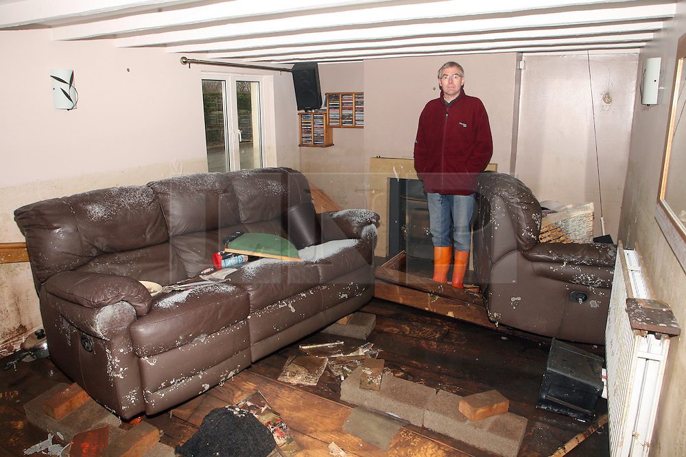 © London News Pictures. 06/03/2014. Moorland, UK. Malcolm and Julie Shovel pictured in their home Sunnybank near Moorland in Somerset. after returning to asses damage cause by flooding. Photo credit: Jason Bryant/LNP