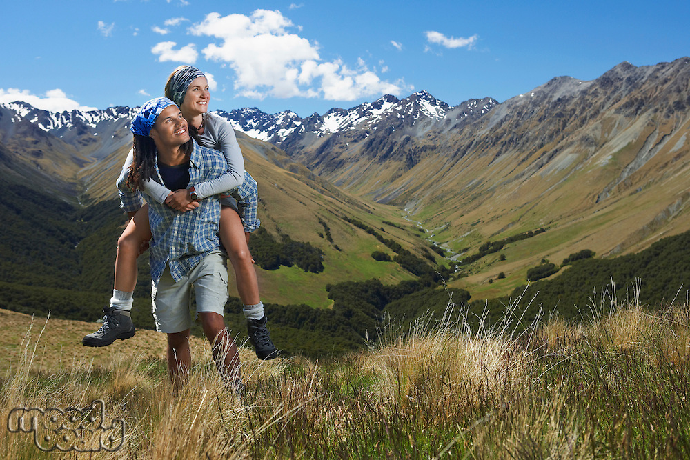 Man giving woman piggy-back ride up hill with mountains behind