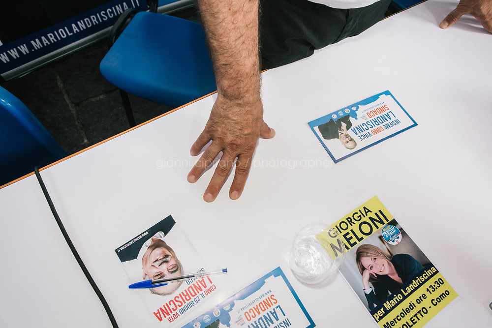 COMO, ITALY - 21 JUNE 2017: Flyers of Giorgia Meloni (leader of the Fratelli d&rsquo;Italia party) and of Mario Landriscina (the leading candidate for Mayor of Como who wants to close the migrants reception center), are seen here at Mr Landriscina's rally in Como, Italy, on June 21st 2017.<br /> <br /> Residents of Como are worried that funds redirected to migrants deprived the town&rsquo;s handicapped of services and complained that any protest prompted accusations of racism.<br /> <br /> Throughout Italy, run-off mayoral elections on Sunday will be considered bellwethers for upcoming national elections and immigration has again emerged as a burning issue.<br /> <br /> Italy has registered more than 70,000 migrants this year, 27 percent more than it did by this time in 2016, when a record 181,000 migrants arrived. Waves of migrants continue to make the perilous, and often fatal, crossing to southern Italy from Africa, South Asia and the Middle East, seeing Italy as the gateway to Europe.<br /> <br /> While migrants spoke of their appreciation of Italy&rsquo;s humanitarian efforts to save them from the Mediterranean Sea, they also expressed exhaustion with the country&rsquo;s intricate web of permits and papers and European rules that required them to stay in the country that first documented them.