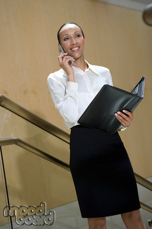 Business woman using mobile phone on stairs