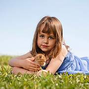 Girl 4-6 years in blue polka dot dress lying on grass looking at camera with kitten
