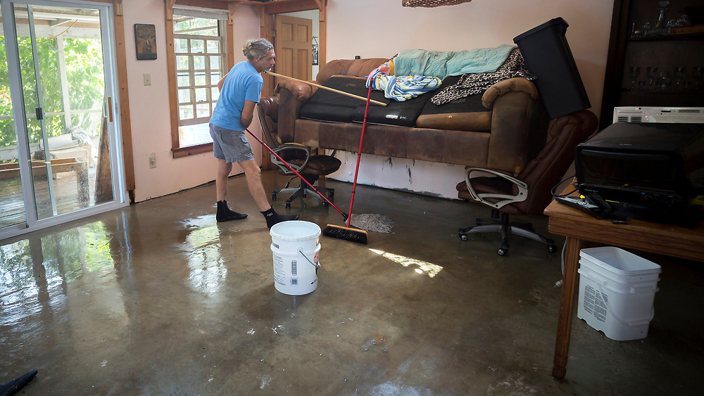 Gene Miles mops under his raised sofa, Tuesday, Sept., 12, 2017, while cleaning up from Tropical Storm Irma on Tybee Island, Ga. (AP Photo/Stephen B. Morton)