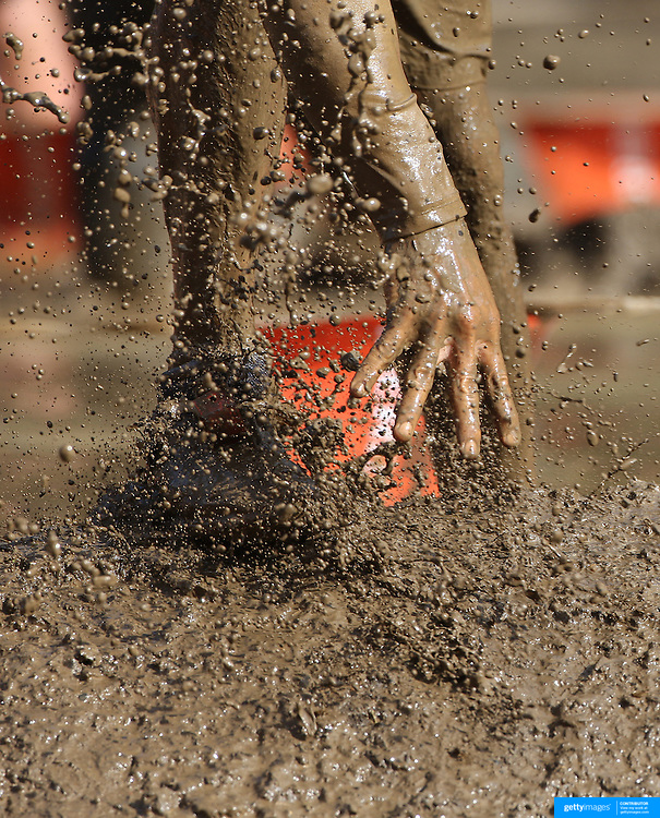 Feet with mud flying as competitors emerge from the mud pit during the New York Merrell Down and Dirty Obstacle Race presented by Subaru. Over 6000 competitors took part in the event which included mud pits, water crossings, slippery mountain, cargo nets, monster climb and ladder walls. The event was held at Pelham Bay Park The Bronx, New York. 29th September 2013. Photo Tim Clayton