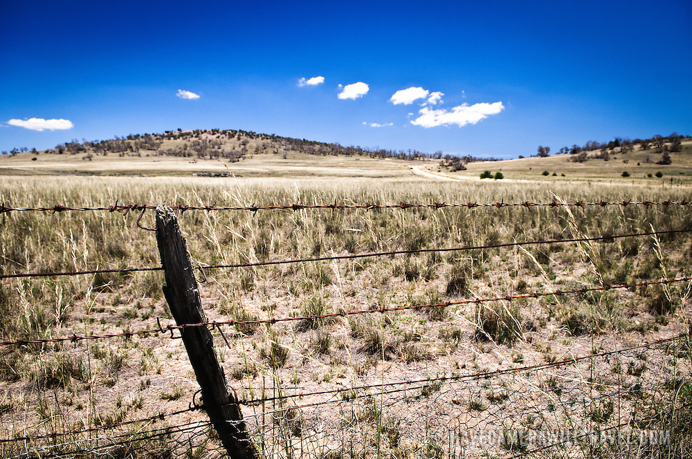 A barbed wire fence around a farm in drought in the Australian outback
