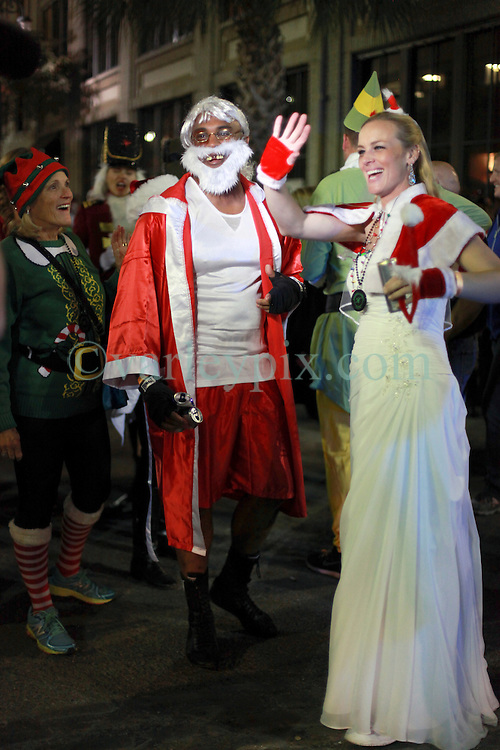 13 December 2014. New Orleans, Louisiana. <br /> just married Jennifer and Garrett Hawk at the 4th annual running of the Santas in downtown New Orleans. Proceeds from the event benefit 'That Others May Love' charity.<br /> Photo; Charlie Varley/varleypix.com