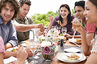 Friends eating drinking and socialising at table outdoors