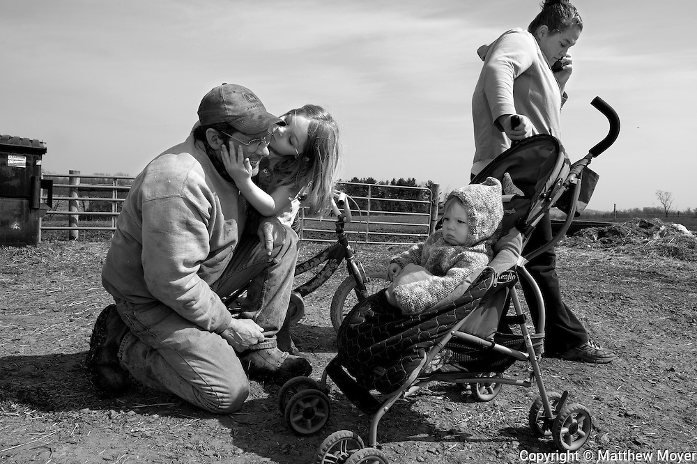 AUBURN, NEW YORK - MARCH 21: Joe Tidd takes a break from working on the family farm to say hi to his grandchildren Emma, 6, and Leah, 8 months, in Auburn, NY March 21, 2010. Joe's daughter in-law, Jen Tidd, stands near-by. The Tidd family has been hit hard by the recent drop in milk prices. They recently had to get rid of their health insurance because it had gotten too expensive.