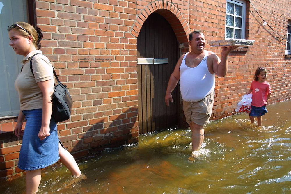 """Local try to enjoy the Elbe floods in hitzacker. Ein Mann trägt mit viel Freude ein Kuchenblech durch die vom """"Jahrhunderthochwasser"""" der Elbe im August 2002 überspülten Innenstadt von Hitzacker."""