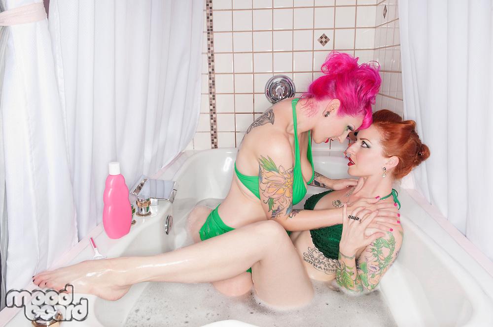 Female seducing other female in the bathtub