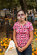 A young girl shows off her Catrina face paint while helping to decorate a gravesite of a family member for the Day of the Dead festival October 31, 2017 in Tzintzuntzan, Michoacan, Mexico.