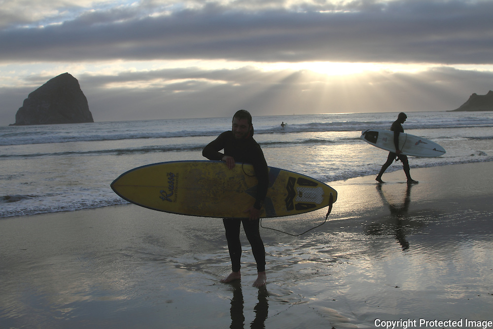 Surfers come in at sunset at Pacific City, Oregon.  Haystack Rock is in the background.