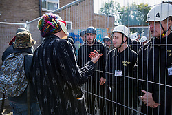 A masked housing activist tries to persuade bailiffs to quit their jobs on the Sweets Way housing estate on 23rd September 2015 in London, United Kingdom. A group of housing activists calling for better social housing provision in London had occupied some of the properties on the 142-home estate in Whetstone, in some cases refurbishing properties intentionally destroyed by the legal owners following eviction of the original residents, in order to try to prevent the eviction of the last resident on the estate and the planned demolition and redevelopment of the entire estate by Barnet Council and Annington Property Ltd.