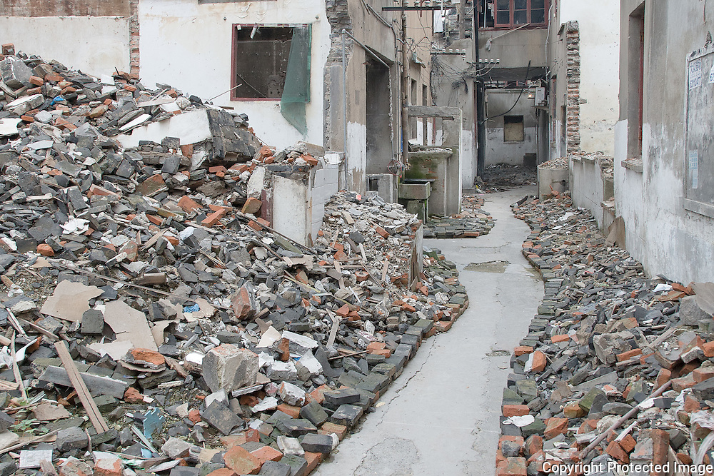 Vanishing Shanghai III. Path through the rubble of demolished houses that are still inhabited before the construction of new buildings. Shanghai, China, 2007