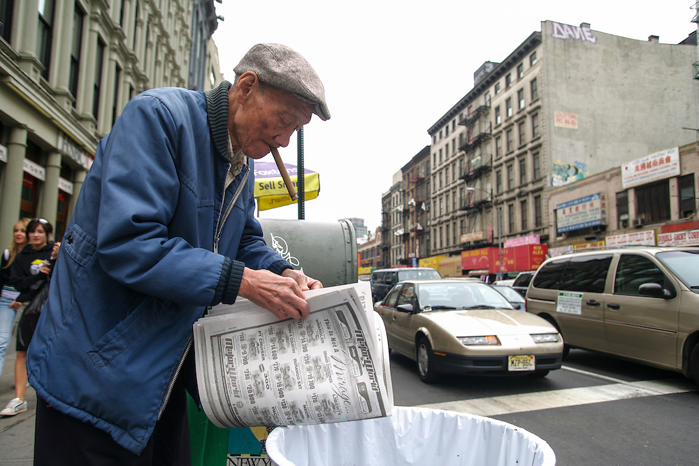 A man reads the newspaper from the litter in New York.