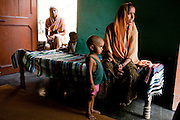 """Shashi Devi (aged 28, right) and her brother-in-law's wife Monika Devi (22, left) sit in their house in the village of Shahpurjat, Ghaziabad, Uttar Pradesh, India. While Shashi had a tubectomy done after having 2 sons, Monika is still trying for a son after having 2 daughters. Shashi did the operation because she wanted to """"give her 2 children the best and inflation will make things difficult"""", and she believes that a """"small family = happy family"""". She has been pushing Monika to get her husband to do an NSV so that Monika's life is not endangered since her previous pregnancies have been complicated. Photo by Suzanne Lee / Panos London"""