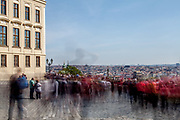 """Crowds walking across """"Hradcany Square"""" (Hradcanske Namesti) towards the panoramic view at the Prague cityscape. On the left Prague Castle."""