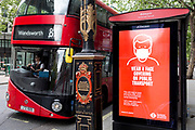 As the UK's Conornavirus pandemic lockdown continues, but with travel restrictions and social distancing rules starting to ease after three months of closures and isolation, a London bus drives past a bus stop where advertising advises the public to wear face coverings on all public transport from June 15th next week, on 9th June 2020, in London, England.