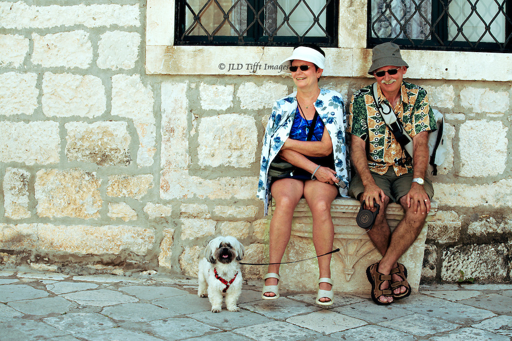 A pair of tourists in shorts and walking shoes resting on the wall of a house in Korcula.  Their pet dog, on a leash, rests next to them.