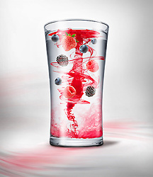 Glass of fruity energy drink being mixed with water.
