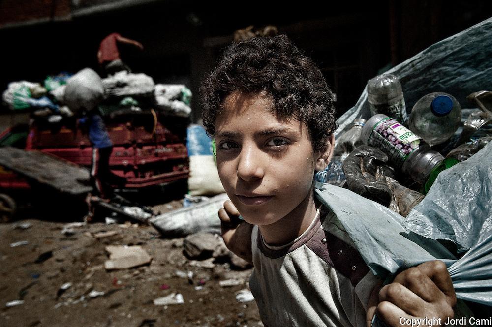"""Joven recolector del barrio de Mokattam . En medio del barrio de Manshiet Nasr a las afueras de El Cairo esta situado el asentamiento de Mokattam conocido como la """"Ciudad de la Basura"""" , está habitado por los Zabbaleen ,una comunidad de unos 45.000 cristianos coptos que viven desde hace varias décadas de reciclar los desperdicios que genera la capital egipcia: plástico, aluminio, papel y desechos órganicos que transforman en compost . La mayoría forman parte de la Asociación para la Protección del Ambiente (APE) una ONG que actúa en el área, cuyos objetivos son proteger el medio ambiente y aumentar el sustento de las recuperadores de basura de El Cairo. Según la ONU, el trabajo que se realiza en Mokattam como uno de los diez mejores ejemplos del mundo en el mejoramiento medioambiental. El Cairo , Egipto, Junio 2011. ( Foto : Jordi Camí )"""
