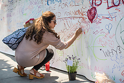© Licensed to London News Pictures. 20/06/2017. London, UK. A woman writes a message of support outside Finsbury Park Mosque in North London. A man drove a white van into a crowd of Muslims in Finsbury Park after Ramadan prayers early on the morning of Monday 19 June 2017, killing one man and injuring a number of others. Photo credit: Rob Pinney/LNP