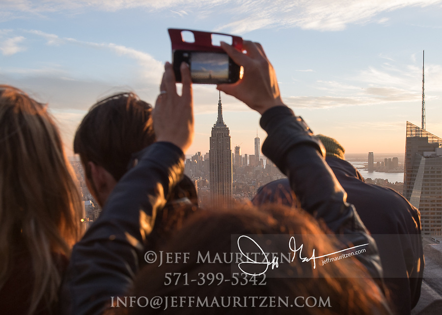 A person takes a photo with a smartphone of sunset over the Empire State Buildling and midtown Manhattan, NYC.