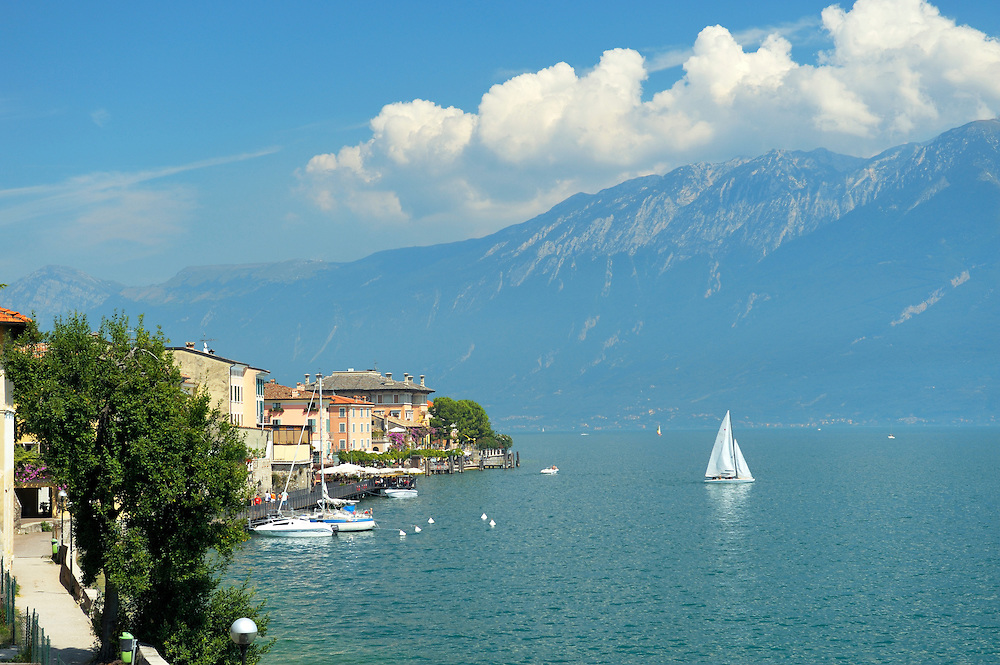The holiday resort town of Gargnano on Lake Garda, Lombardy, Italy. Sail boat leaving the harbour. Lago di Garda.