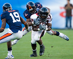 Virginia cornerback Vic Hall (4) jumps on the back of Texas Tech running back Aaron Crawford (32).  The Texas Tech Red Raiders defeated the Virginia Cavaliers 31-28 in the 2008 Konica Menolta Gator Bowl held at the Jacksonville Municipal Stadium in Jacksonville, FL on January 1, 2008.