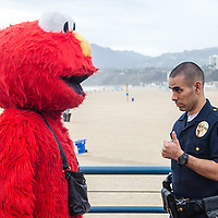 A Santa Monica Police Officer talks to Elmo about complaints from the public at the Santa Monica Pier on Friday, February 27, 2015.