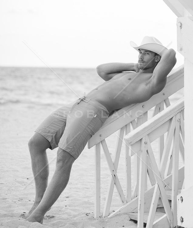 sexy man reclining on a lifeguard stand railing at the beach