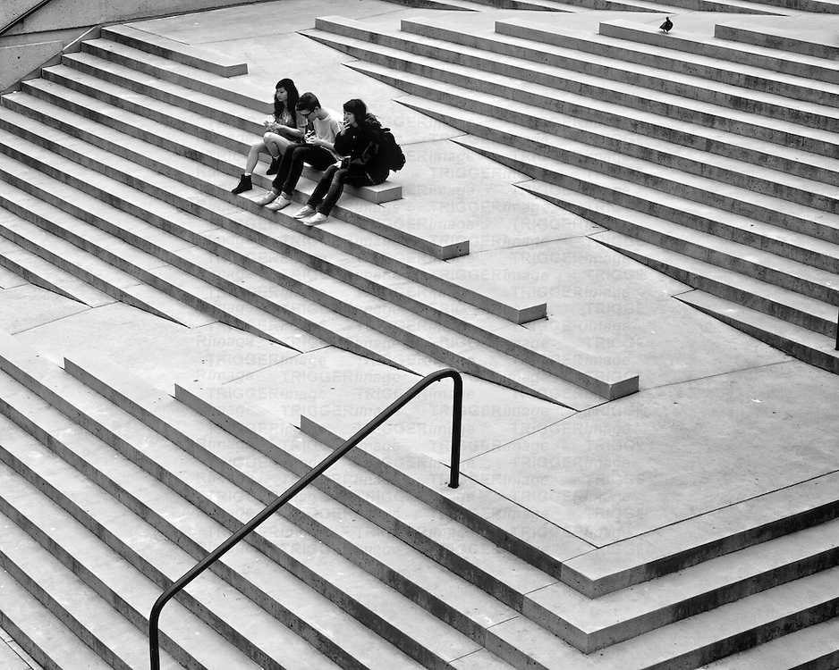 Three friends, and a bird hanging out on architectural stairs.