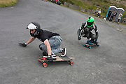 Two long boarders descend a hill on private road in Tregaron, Wales.