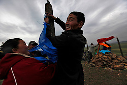 Mongolian worshippers tie colored scarves to poles surrounding the as the 'Ovoo' or 'sacred stone' site for Mongolian Shaman brothers Gankhuyag and Batgerel Batmunkh during a  Shaman ceremony by  on Black Mountain Head in Nalaikh district of Ulan Bator in Mongolia, 06 July 2012. The Shaman ceremony is held for a family to give offerings to the spirits of nature and to bring good karma to the members of family. The color blue is symbolic of the 'open sky' or 'Tengri' while red represents 'fire'; orange for 'sand' and white for 'milk'. Shamanism comes from the term 'shamans' that refers to priests or mediums that acts as vessels for spirits, gods and demons to communicate with the human world. In Mongolia, they adhere to the ancient beliefs of Tengrism, where spirits live in all of nature, in the sun, moon, lakes, rivers, mountains, and trees.