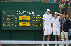 LONDON, ENGLAND - Thursday, June 24, 2010: John Isner (USA) poses with Nicolas Mahut and Umpire Mohamed Lahyani next to the scoreboard after the historic longert game ever that lasted 11 hours and five minutes over three days. He beat Nicolas Mahut with the final score of 6-4 3-6 6-7 (7-9) 7-6 (7-3) 70-68 on day four of the Wimbledon Lawn Tennis Championships at the All England Lawn Tennis and Croquet Club. (Pic by David Rawcliffe/Propaganda)