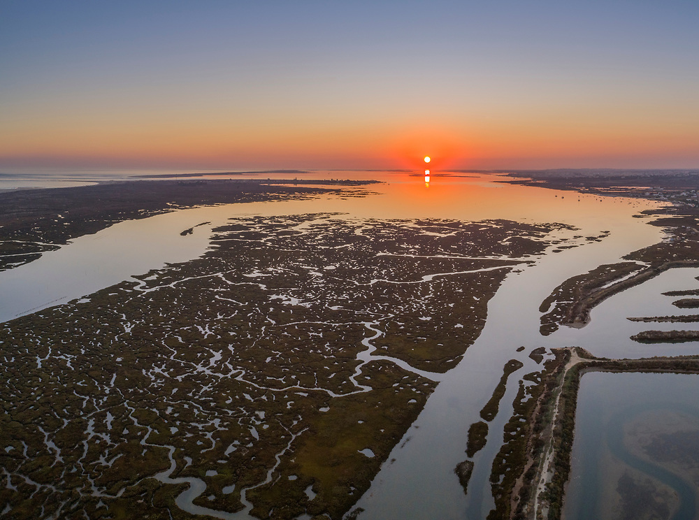Aerial sunset seascape in Ria Formosa wetlands natural park, inland maritime channel. Algarve. Portugal.