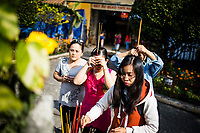 People pray to a small alter in the middle of Binh Tay market in District 5, Ho Chi Minh City, Vietnam.