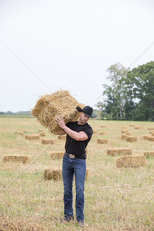 rugged working cowboy on a ranch with hay