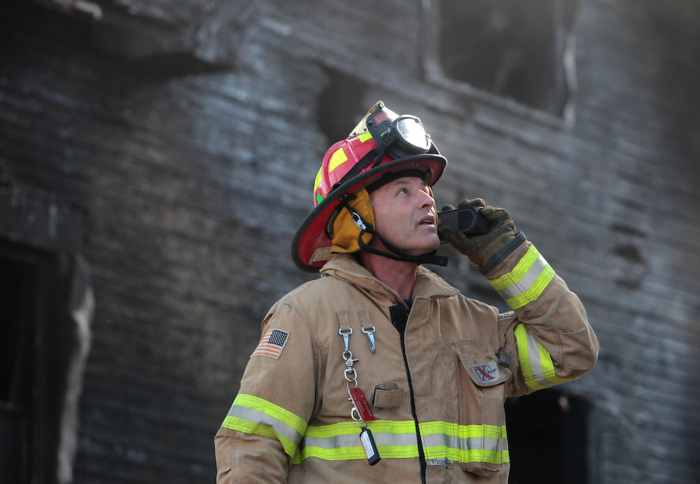 A firefighter talks on the radio as a house burns at 7th and Elm Street in Muncie afternoon. The fire also spread to the neighboring house. No one was injured but the fire is being investigated as arson. .(Chris Bergin/ The Star Press)