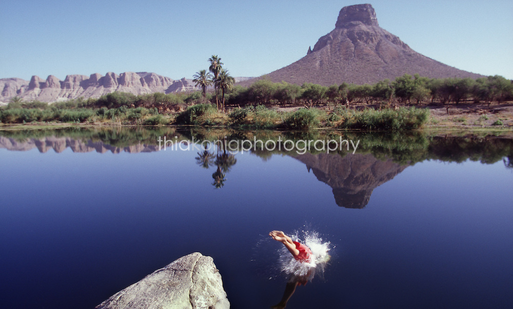 Man in red shorts dives into a perfectly still lake in the desert, Baja Mexico. Only legs and splash with perfect reflection is above water.