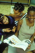Young black women looking at a magazine, laughing, UK 1990's.