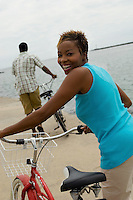 Woman with bicycle at beach (portrait)